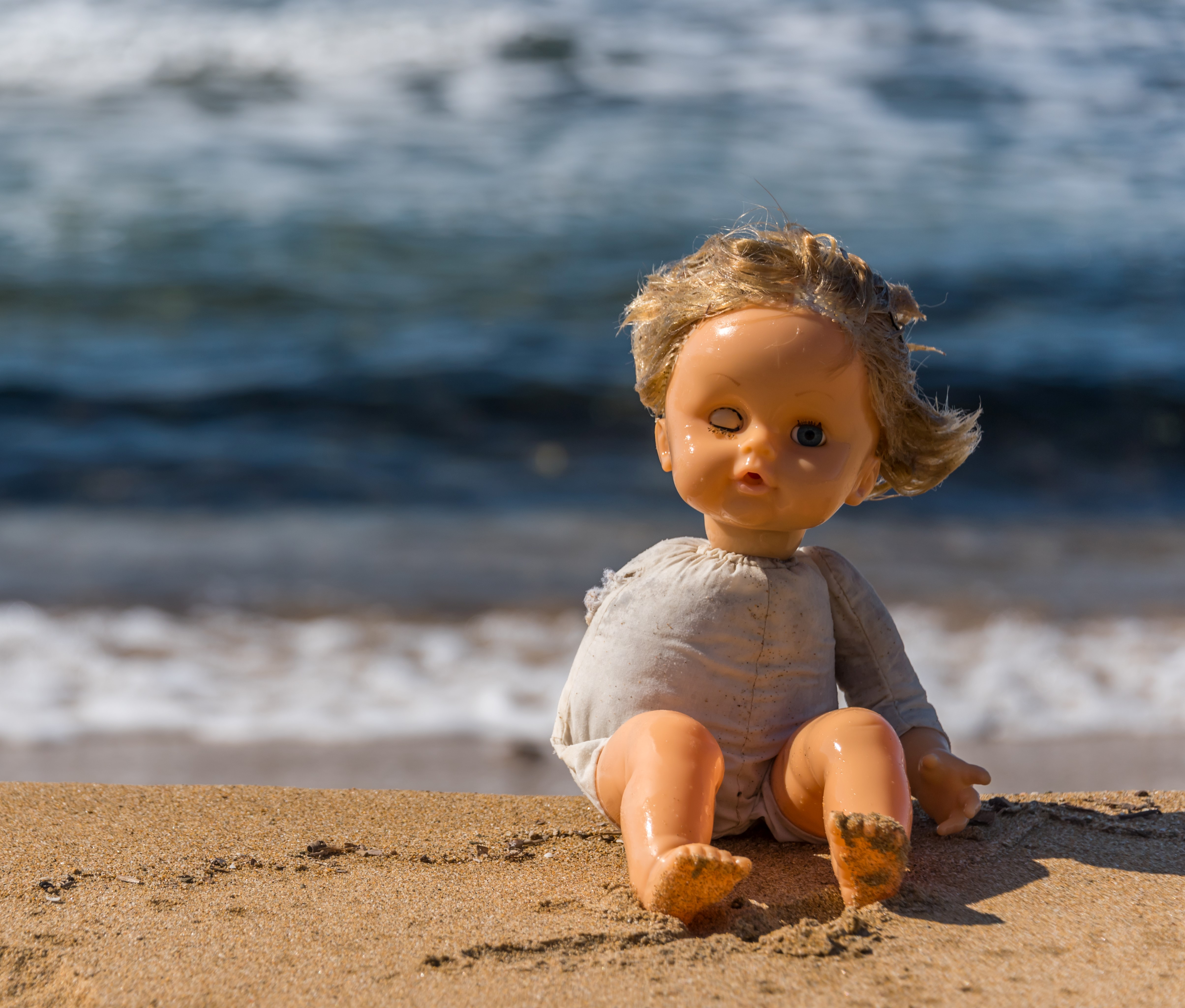 Old Broken Toy Doll Sitting on a Beach in Italy